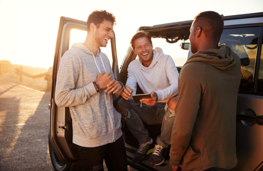 three men sitting in and standing next to car laughing