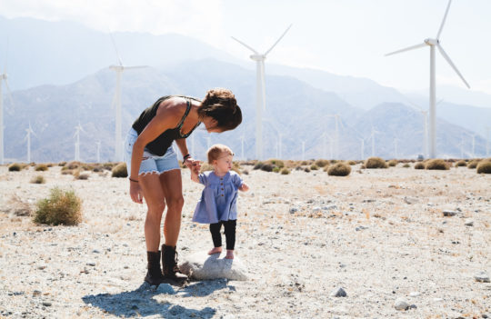 mother and child with windmills in background