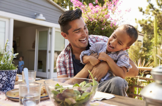 father and son laughing after meal outdoors